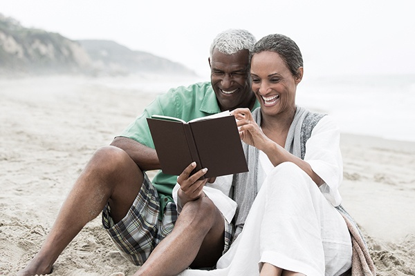 Older man and woman reading together on beach