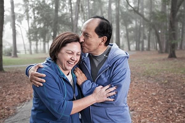 Man kissing woman's forehead while walking through a park