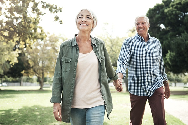 older woman and man holding hands while walking outdoors