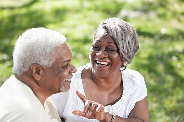 older woman and man laughing together outdoors