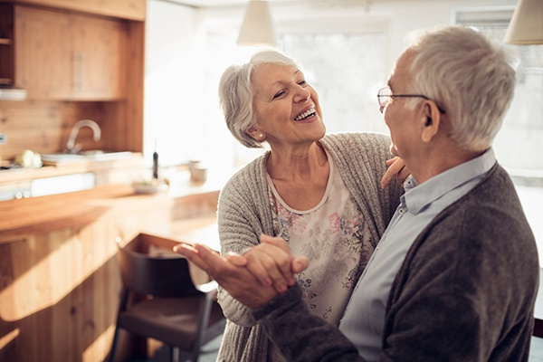 older man and woman dancing together in kitchen