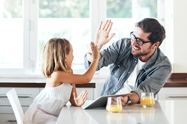 dad high-fiving daughter while holding tablet