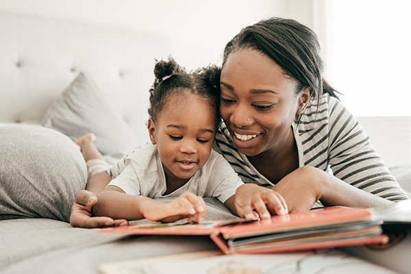mom reading with daughter in bed
