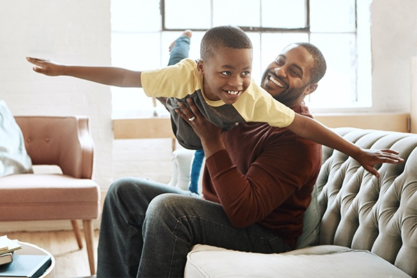 dad playing with son on sofa