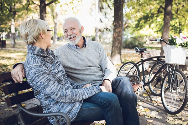 older man and woman sitting together on park bench