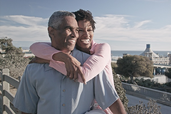 woman with arms around man near the ocean