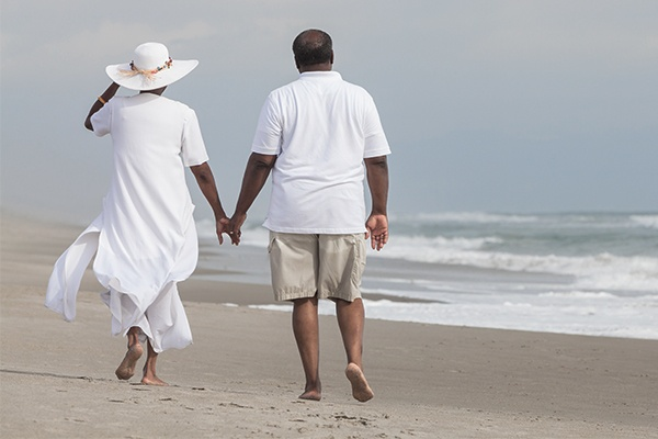 man and woman walking on beach holding hands